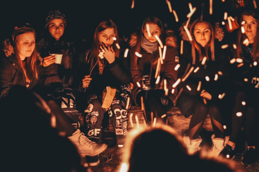 group of teenage girls sitting around a camp fire at night.