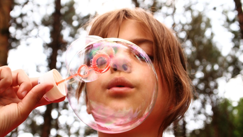 young girl blowing a large bubble